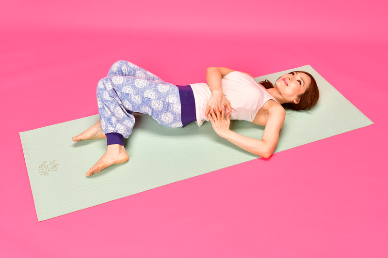 仰向けになって膝を立て、両手を肋骨と骨盤の間に置き体を右に傾ける女性