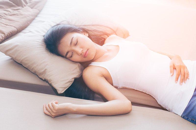 ベッドで寝ているタンクトップ姿の女性