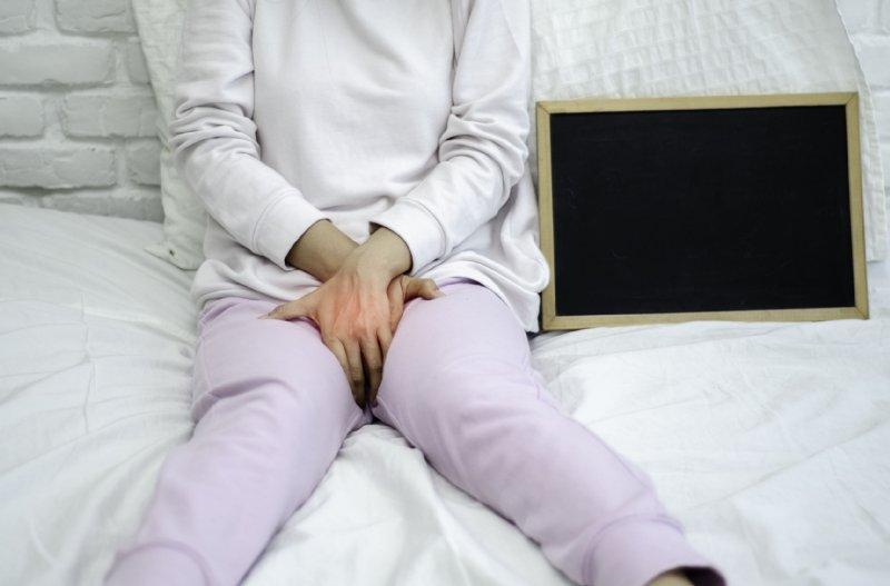 ベッドぬ座って、股のあたりを両手でおさえる女性