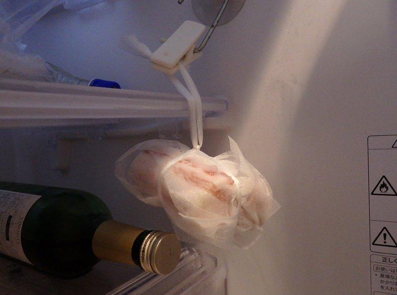 冷蔵庫に吊るされた豚バラ肉の塊