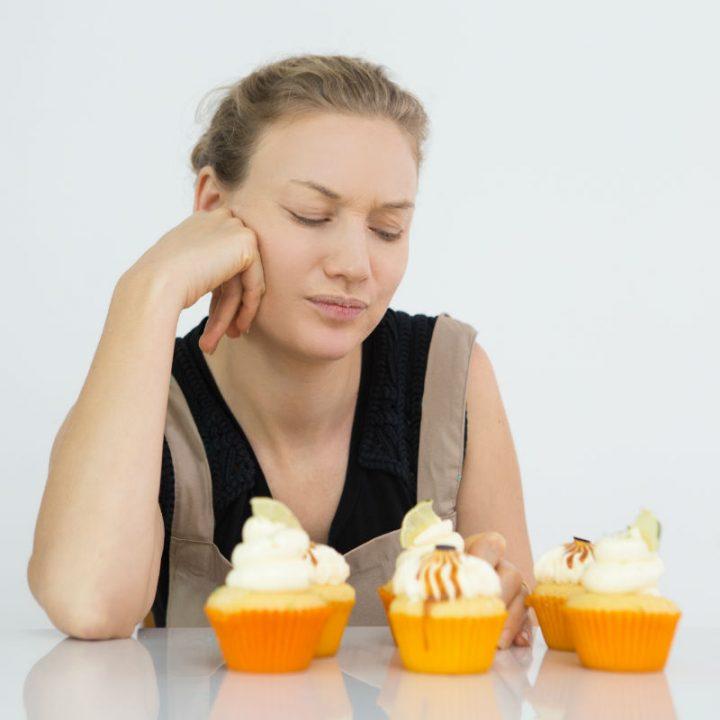 カップケーキを見つめる女性