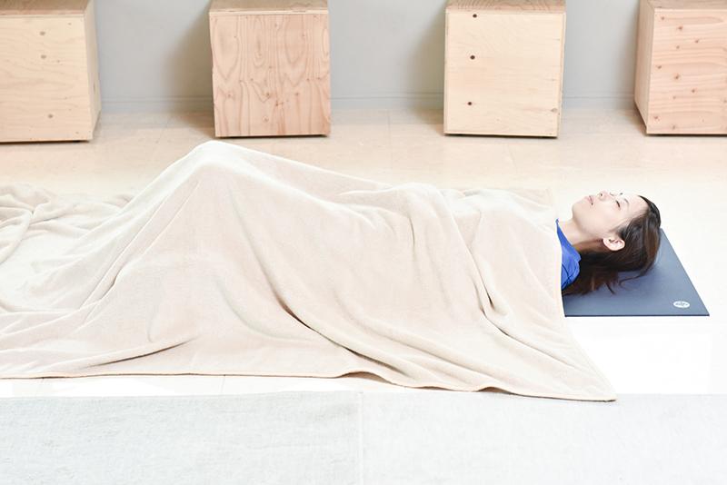 マットの上に女性が横になって目をつぶっている。タオルケットをかけられている