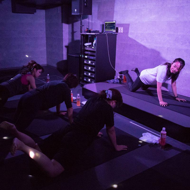 『EXPA(エクスパ)』のレッスン風景。女性トレーナー、受講者が床に手をついている