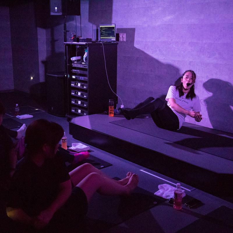 『EXPA(エクスパ)』のレッスン風景。暗い中でのレッスン。女性トレーナーと受講者が腹筋を鍛える動きをしている