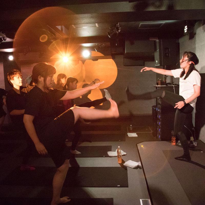『EXPA(エクスパ)』のレッスン風景。暗い中でのレッスン。女性トレーナーと受講者が足を上げる動きをしている