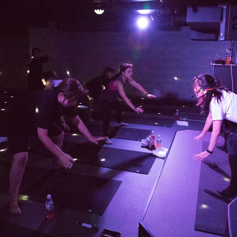 『EXPA(エクスパ)』のレッスン風景。暗い中でのレッスン。女性トレーナーと受講者が両手を床につけようとする動きをしている