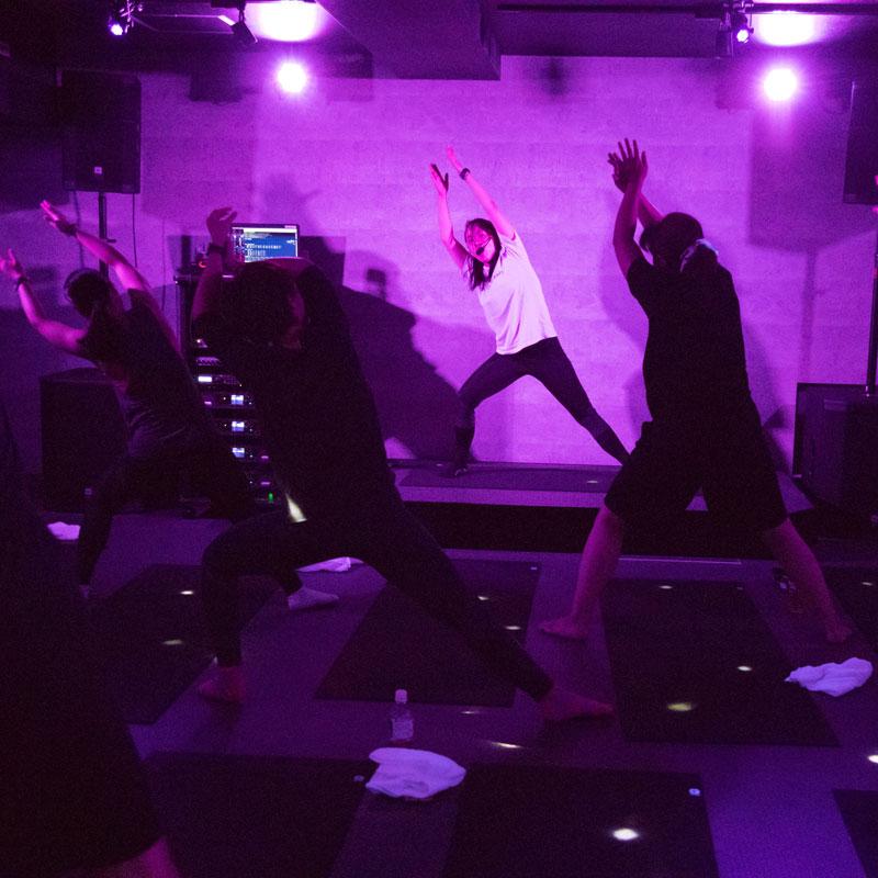 『EXPA(エクスパ)』のレッスン風景。暗い中でのレッスン。女性トレーナーと受講者が両腕を上に大きくあげている