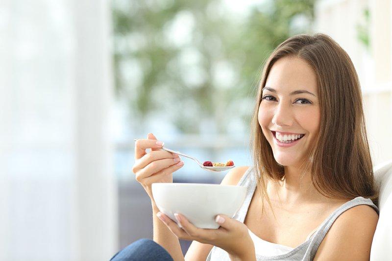 ヨーグとをスプーンで食べる女性