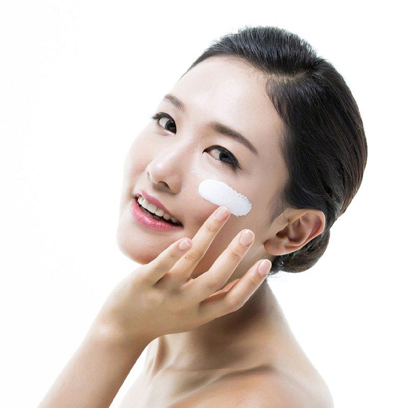 顔に日焼け止めクリームを塗る女性