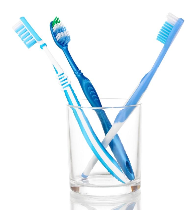 コップに置かれている3本の歯ブラシ