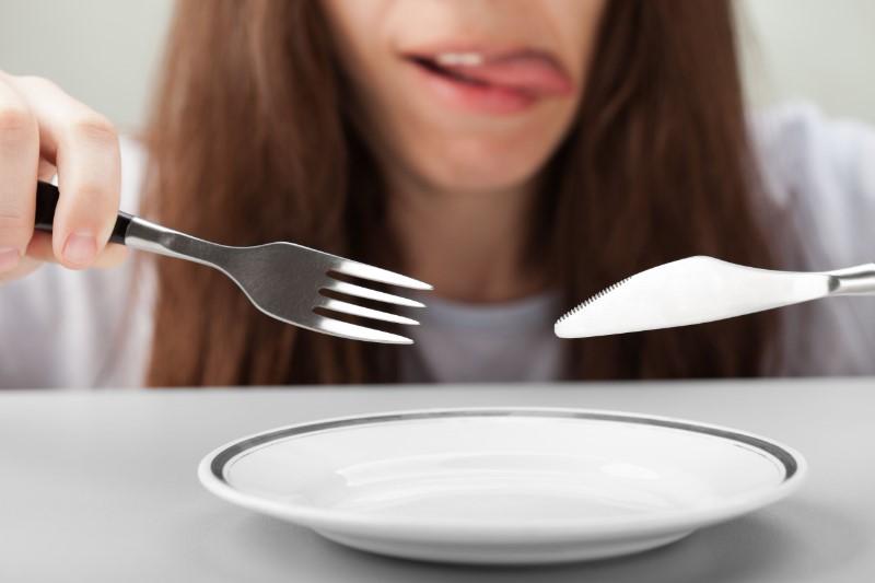 空のお皿にナイフとフォークで食べようとする女性のアップ