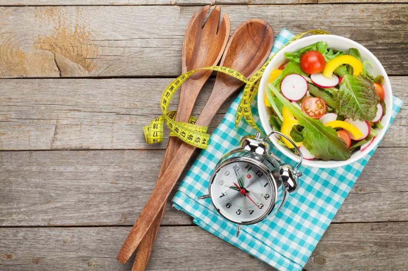 ナプキンの上にサラダ、木のナイフとフォーク、時計がある