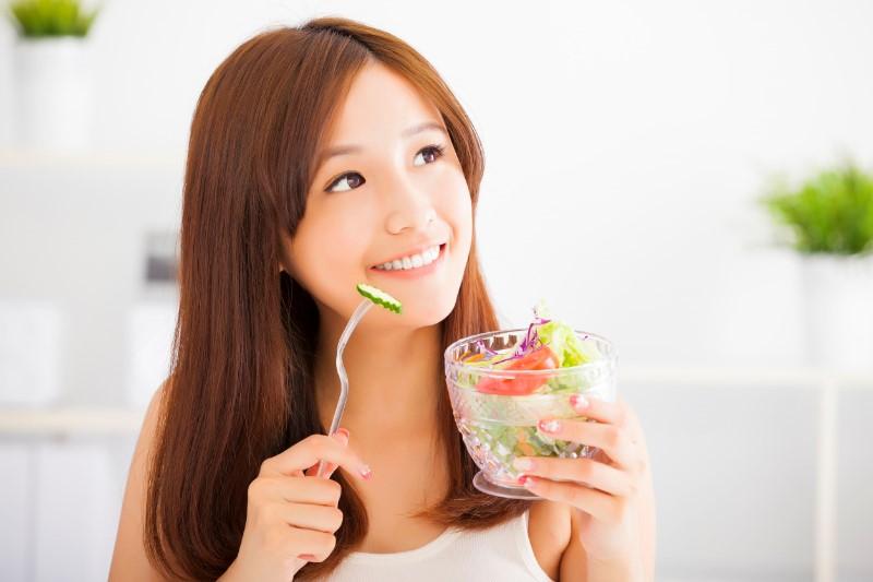 サラダをフォークで食べる女性