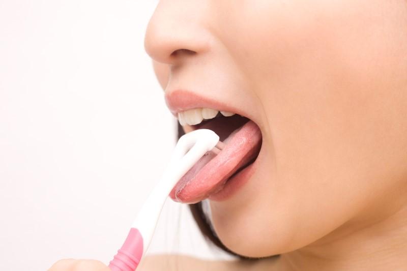 舌磨きをする女性の口のアップ