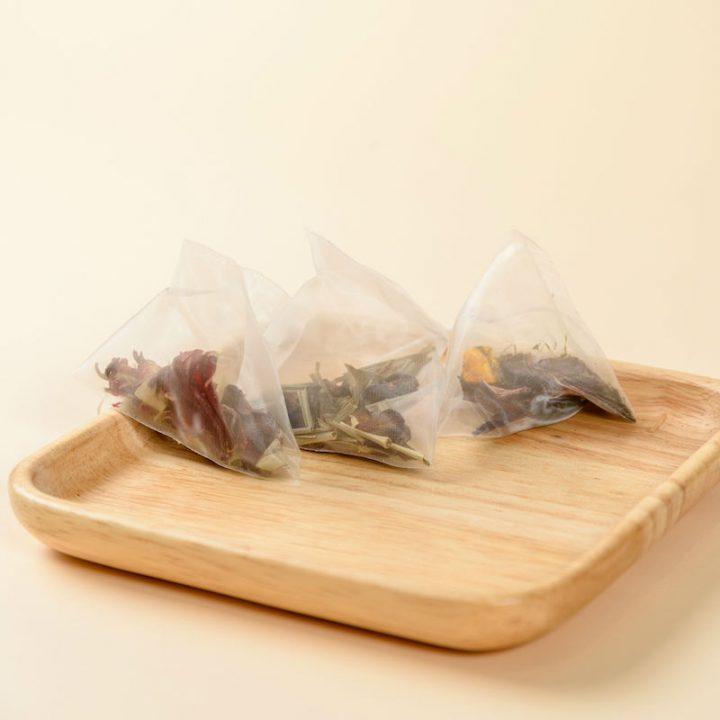 木皿に3つ並べた『natoha(ナトハ)黒人参茶』のティーバッグ