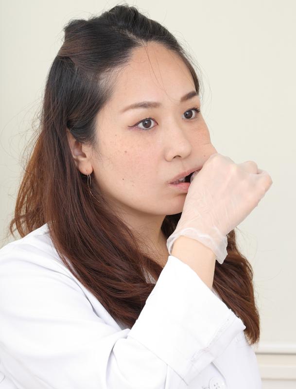 顔の下半分の筋肉をほぐす白衣の女医