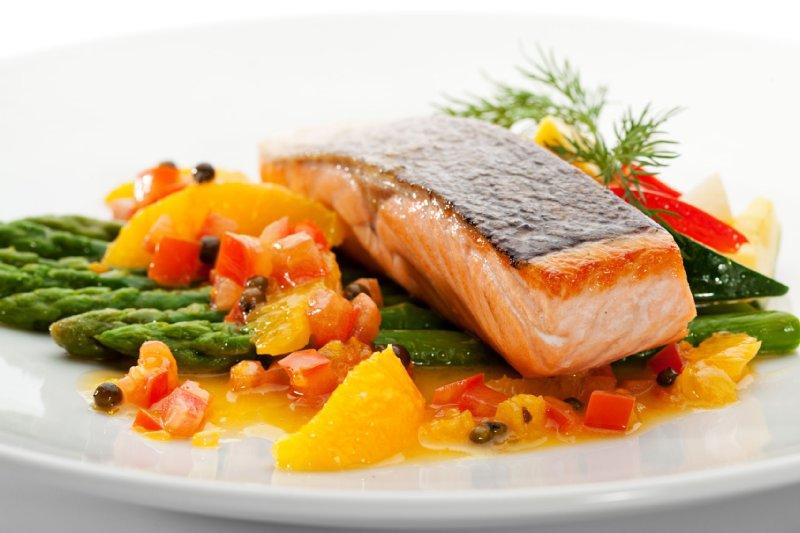 アスパラと野菜ソースの上に焼いた鮭が載った料理