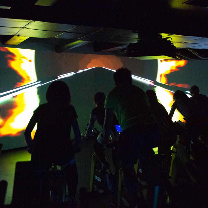 「CYCLE & STUDIO R」VRサイクル『THE TRIP』の画面と体験者の後ろ姿