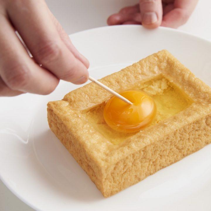 くり抜いた厚揚げに卵を落とし、つまようじで黄身に穴を開ける