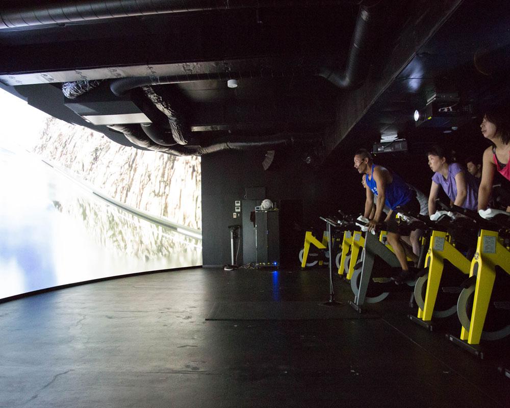 「CYCLE & STUDIO R」VRサイクル『THE TRIP』の画面と体験者を横から見た様子