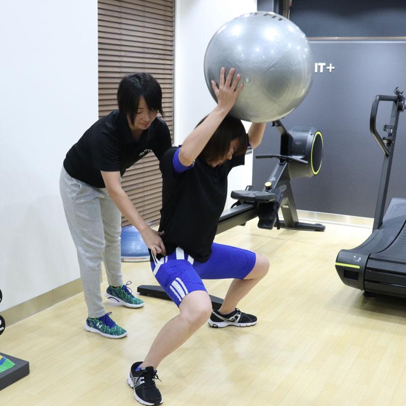 トレーナーの指導の元、両手でボールを頭上に持ってトレーニングを行うライターF