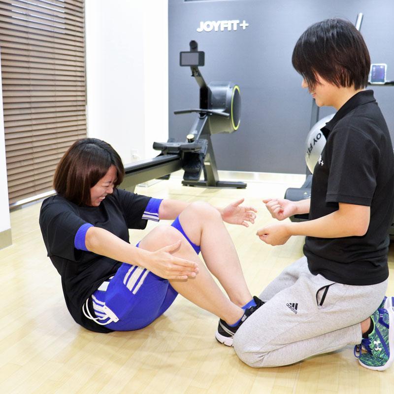トレーナーの指導の元、腹筋を行うライターF