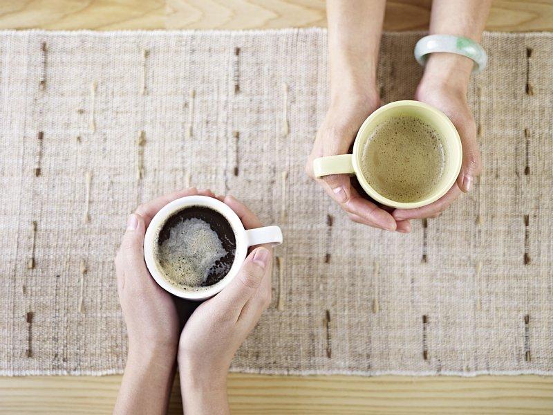 手に持ったカップに入ったコーヒーと手に持ったカップに入った緑茶
