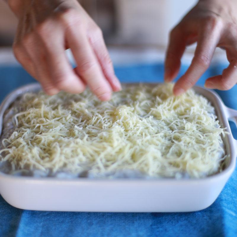手のアップと作っている途中の里芋グラタンのアップ