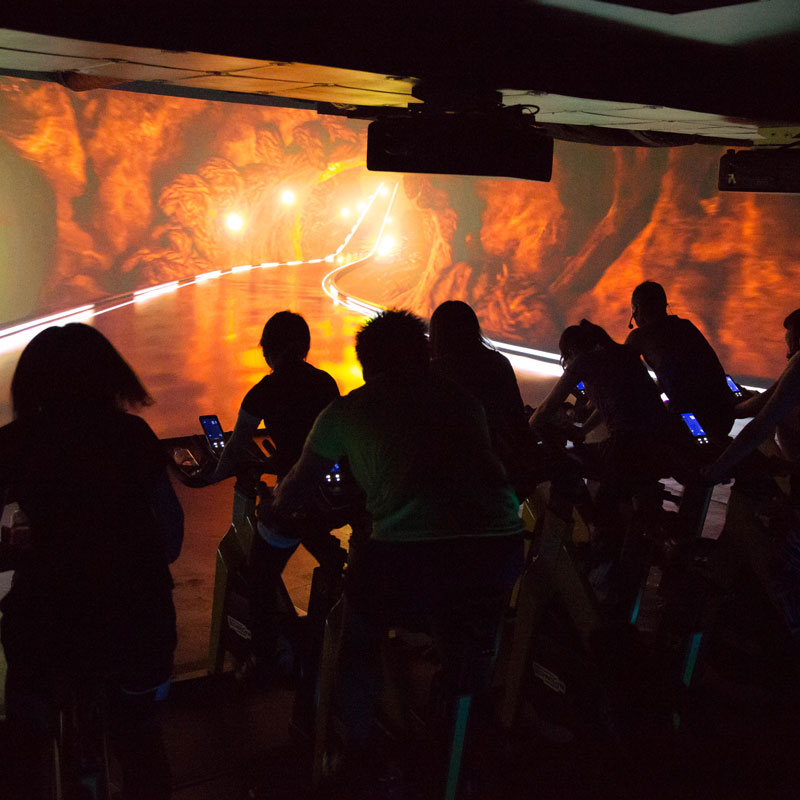 「CYCLE & STUDIO R」VRサイクル『THE TRIP』の火山コースの画面と体験者の後ろ姿