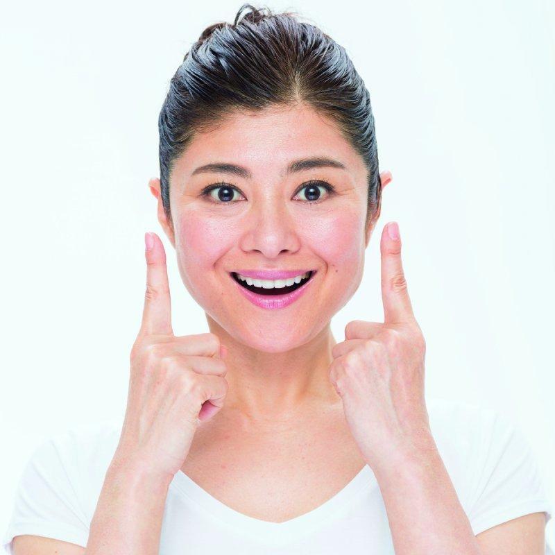 両人差し指を両頬から離れてもってきて、口角を上げたままの間々田佳子さん