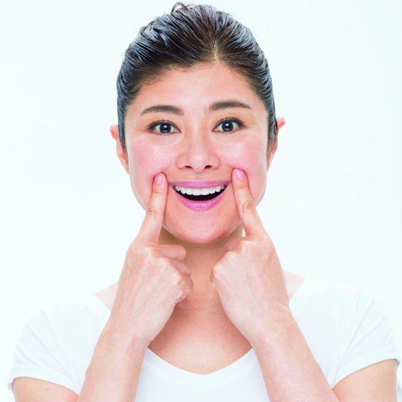 人さし指で、口角を持ち上げて、上の歯8本を見せて笑う間々田佳子さん