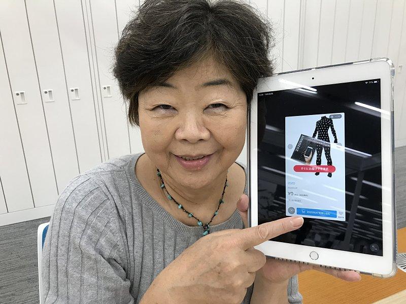 iPadを持ち、ZOZOSUITを注文するオバ記者