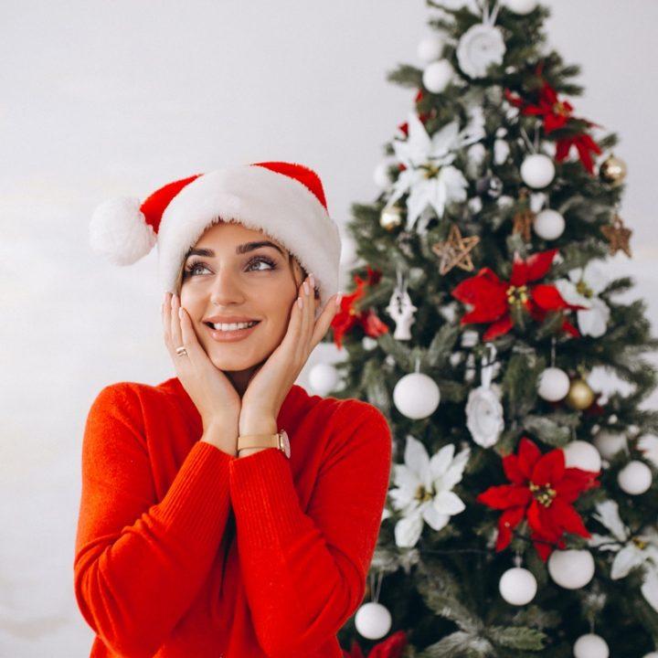 クリスマスツリーとサンタ帽をかぶった女性