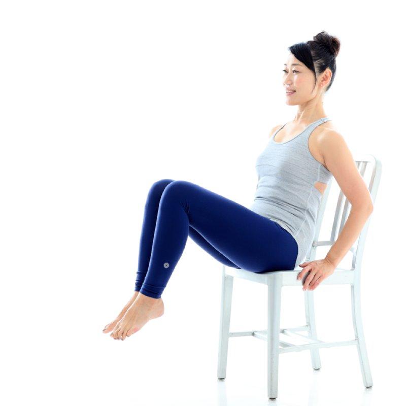 両手で椅子の座面をつかみ、体を少し後傾させて両足をそろえて浮かせている