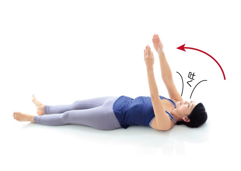 寝た状態で腕をまっすぐ体の前に伸ばし、前へならえのポーズをしている