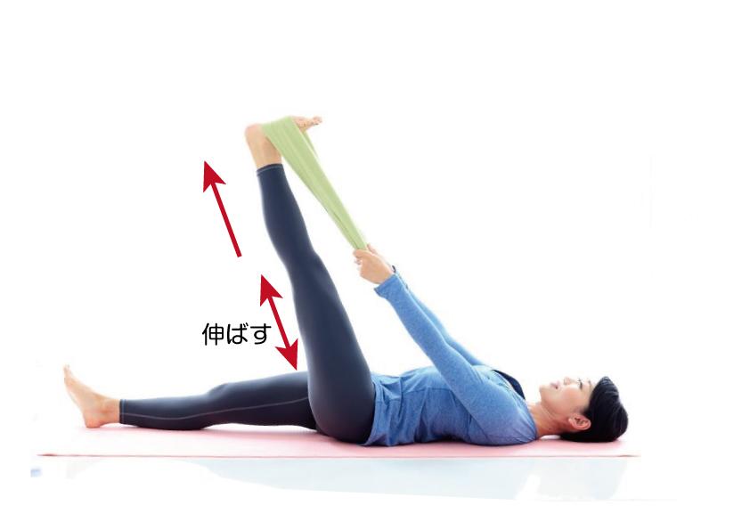 仰向けになって左足を上げ、足裏にタオルをひっかけまっすぐに伸ばしている
