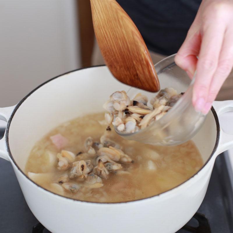 煮立った鍋に白いミネストローネの材料を入れている