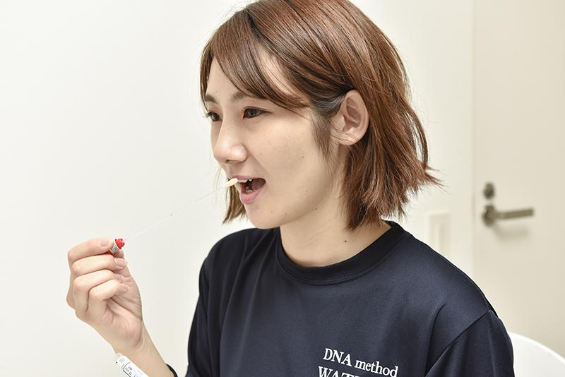遺伝子検査をする器具を手にする女性体験者