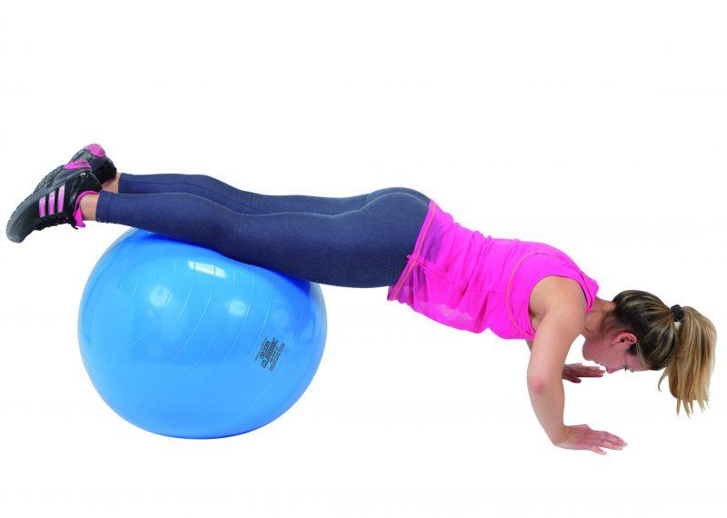 女性がギムニクボール65に足を乗せて腕立て伏せをしている