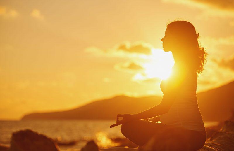 夕方に海辺で女性が瞑想をしている
