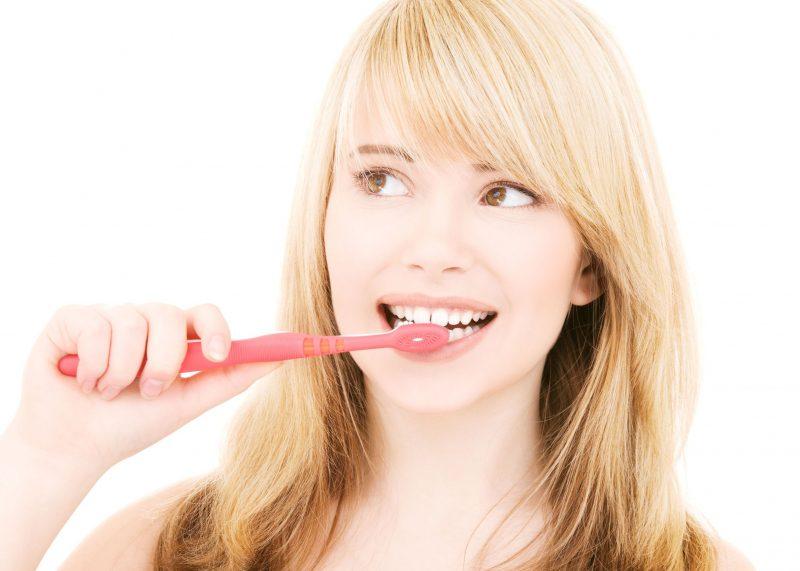 女性が赤い歯ブラシで歯みがきをしている