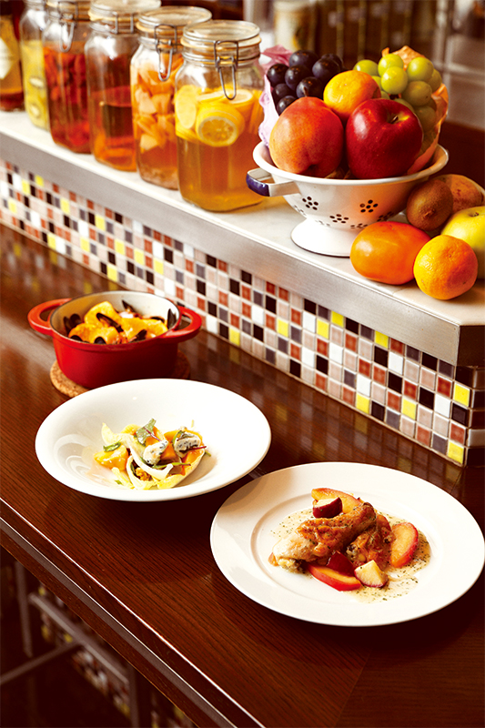 リンゴのフリカッセ、柿のチーズあえサラダ、みかん入りパエリアなどフルーツ料理がテーブルに並ぶ