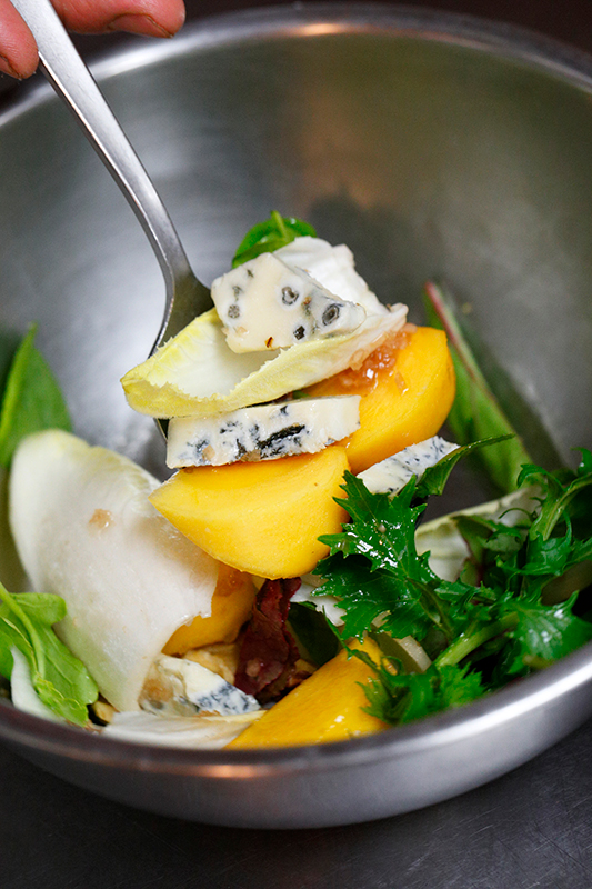 ボウルで柿、ゴルゴンゾーラチーズ、チコリ、ルッコラなどをあえてサラダを作っている
