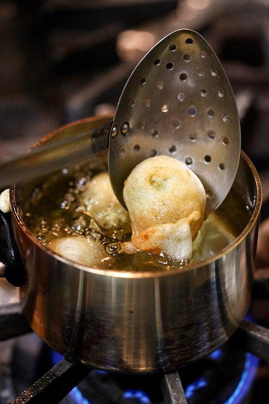 天ぷら衣をまとった白ぶどうを油で揚げている