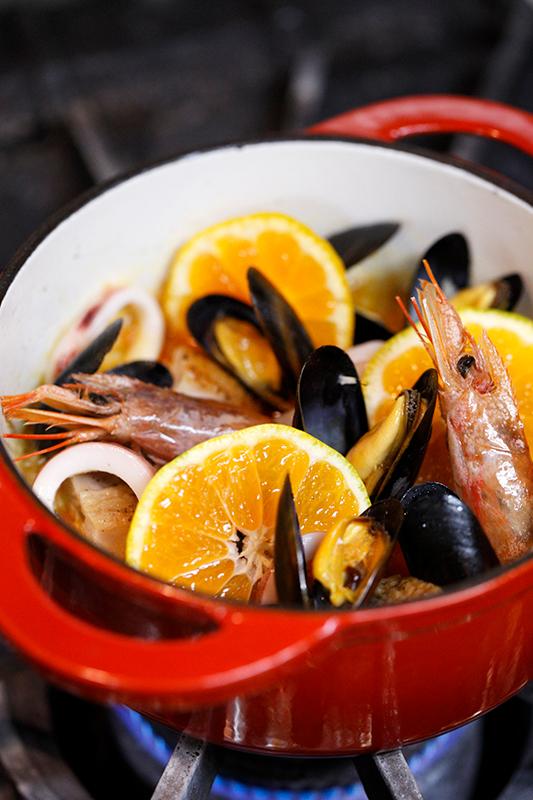 パエリアの鍋でみかん、お米、えび、ムール貝などが炊かれている