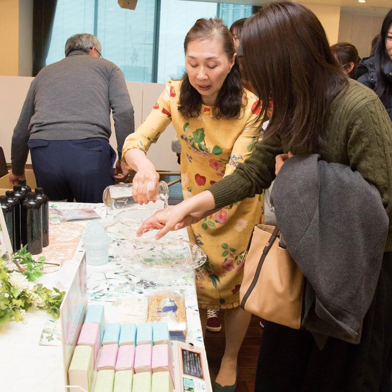 『KOSHIBA石けん』のデモンストレーションを受ける女性