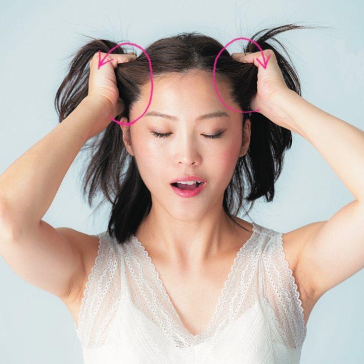 髪の毛を引っ張り、マッサージする女性