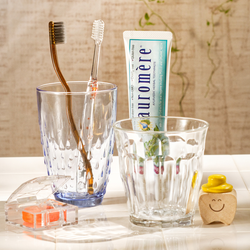グラスと歯ブラシ、歯磨き粉が置かれている