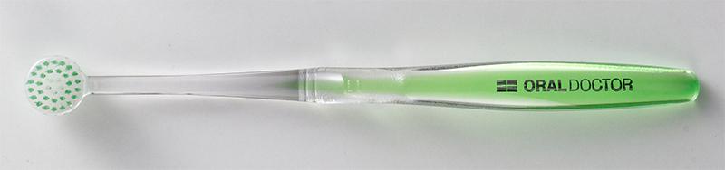透明の持ち手に、緑色の毛が円形に植えられている歯ブラシ