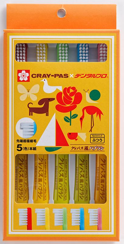 クレパスのようなデザインのケースに入っている、赤、黄、緑、青、ピンク色のクレパス風歯ブラシ5本